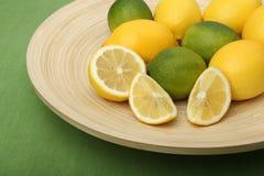 Primo piano dei limoni e delle limette su una zolla di legno su fondo verde Fotografie Stock Libere da Diritti