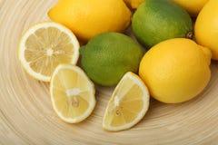 Primo piano dei limoni e delle limette su una zolla di legno su fondo verde Fotografia Stock