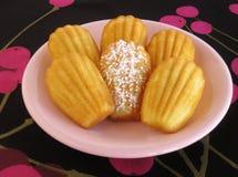 Primo piano dei madeleines francesi classici in piatto d'annata rosa sulla tovaglia nera e magenta moderna del ciliegia-modello fotografie stock libere da diritti