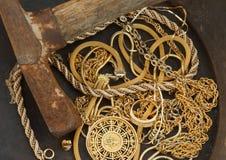 Primo piano dei monili dello scarto in vaschetta dell'oro con il piccone Fotografia Stock