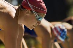 Primo piano dei nuotatori ai blocchetti iniziare Immagini Stock Libere da Diritti