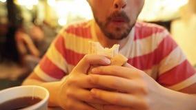 Primo piano dei pantaloni a vita bassa barbuti affamati che mangiano uno shawarma delizioso del pollo stock footage