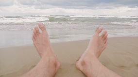 Primo piano dei piedi degli uomini sulla spiaggia Uno sguardo alle onde del mare che vengono alla riva Festa di vacanze estive stock footage