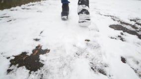 Primo piano dei piedi del ` s dell'uomo che camminano sulla neve video d archivio