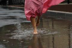 Primo piano dei piedi del ` una s della ragazza che ballano in una pozza dopo una pioggia di estate immagine stock