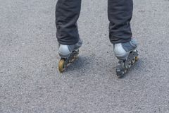 Primo piano dei piedi dell'uomo con la lama del rullo sulla strada Principiante, attività urbana di sport, rulli sulla strada asf fotografia stock libera da diritti
