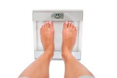 Primo piano dei piedi della donna che misurano peso immagine stock