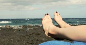 Primo piano dei piedi della donna che si rilassa sulla spiaggia di sabbia nera archivi video