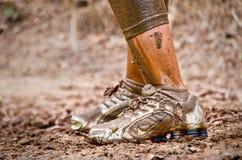 Primo piano dei piedi fangosi del corridore di corsa del fango Immagini Stock