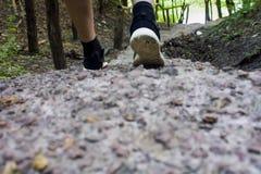 Primo piano dei piedi maschii in scarpe da tennis che corrono all'aperto Fotografia Stock