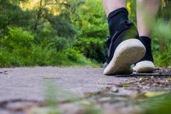 Primo piano dei piedi maschii in scarpe da tennis che corrono all'aperto Immagini Stock