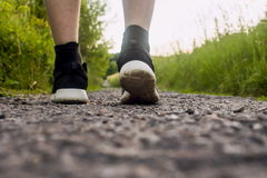 Primo piano dei piedi maschii in scarpe da tennis che corrono all'aperto Immagine Stock Libera da Diritti