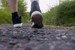 Primo piano dei piedi maschii in scarpe da tennis che corrono all'aperto Immagine Stock
