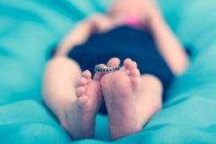 Primo piano dei piedi neonati con una fede nuziale Fotografia Stock