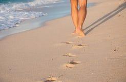 Primo piano dei piedi nudi del ` una s dell'uomo che camminano ad una spiaggia al tramonto, Fotografia Stock