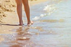 Primo piano dei piedi nudi femminili del ` una s che camminano ad una spiaggia alla mattina Concetto del viaggio, vacanza fotografia stock
