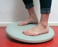 Primo piano dei piedi sotto le blue jeans sul bordo dell'equilibrio Immagini Stock