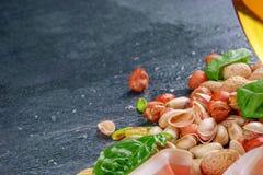 Primo piano dei pistacchi incrinati salati saporiti, delle foglie fresche del basilico e dei dadi croccanti su un fondo grigio Sp Immagine Stock