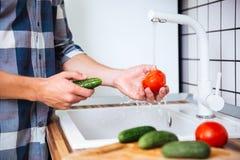 Primo piano dei pomodori e dei cetrioli di lavaggio dell'uomo sulla cucina Fotografia Stock Libera da Diritti