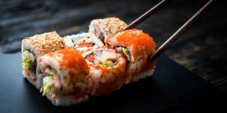 Primo piano dei rotoli di sushi con i bastoncini Fotografie Stock Libere da Diritti