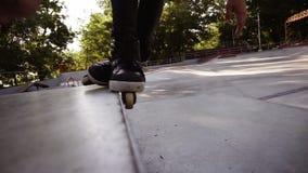 Primo piano dei rulli dell'uomo sull'orlo del parapetto Giovane rullo che esegue le acrobazie sui pattini, sugli scorrevoli e sul archivi video