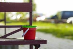 Primo piano dei secchi rossi e verdi di plastica del giocattolo del bambino su vecchio marrone Fotografia Stock