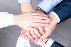 Primo piano dei soci commerciali che fanno mucchio delle mani alla riunione Fotografia Stock