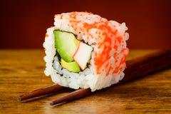 Primo piano dei sushi di Uramaki sui bastoncini Fotografie Stock