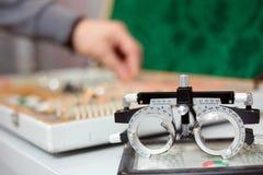 Primo piano dei vetri antiquati della prova dell'occhio che stanno su un grafico di occhio immagini stock