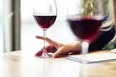 Primo piano dei vetri di vino rosso in un caffè Riunione degli amici dell'interno Busta di carta dei pantaloni a vita bassa Immagini Stock Libere da Diritti
