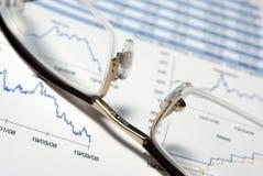 Primo piano dei vetri e del rapporto finanziario. Fotografia Stock