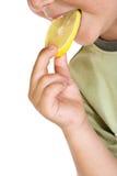 Primo piano del bambino che mangia la fetta del limone Fotografia Stock Libera da Diritti