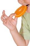 Primo piano del bambino che mangia una fetta arancione Immagini Stock Libere da Diritti