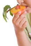 Primo piano del bambino che mangia una pesca mezza Immagini Stock