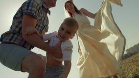 Primo piano del bambino felice che è gettato nell'aria parecchie volte Tutta la famiglia gode del processo archivi video