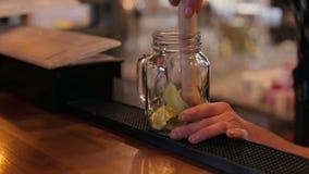 Primo piano del barista che fa i cocktail di Mojito con calce, la menta ed il rum nella barra video d archivio