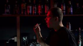 Primo piano del barista maschio che soffia sui carboni nella barra del narghil? stock footage
