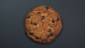 Primo piano del biscotto di pepita di cioccolato, macro colpo, filante lentamente su un fondo nero girante stock footage