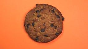 Primo piano del biscotto di pepita di cioccolato, macro colpo, filatura veloce su un fondo arancio girante stock footage