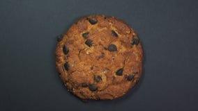 Primo piano del biscotto di pepita di cioccolato, macro colpo, filatura veloce su un fondo nero girante stock footage