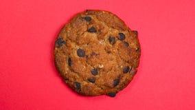 Primo piano del biscotto di pepita di cioccolato, macro colpo, filatura veloce su un fondo rosso girante video d archivio