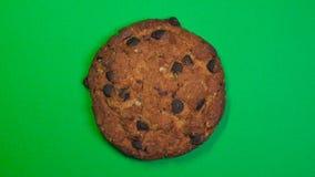 Primo piano del biscotto di pepita di cioccolato, macro colpo, filatura veloce su un fondo verde girante stock footage