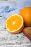 Primo piano del bordo arancio e di legno sano intelligente e del tovagliolo blu su un fondo di legno leggero Immagini Stock Libere da Diritti