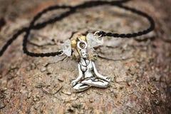 Primo piano del braccialetto con la ragazza di yoga nella posizione di loto fotografia stock