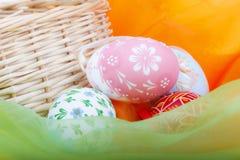 Primo piano del canestro strawy con le uova di Pasqua ed il velluto Fotografia Stock