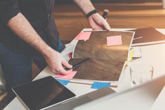 Primo piano del catalogo dei materiali di rifinitura in mani maschii Uomo che sta tavola vicina, sfogliante libro fotografia stock