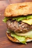 Primo piano del cheeseburger sulla tavola di legno Fotografia Stock