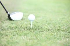 Primo piano del club di golf e del T con la palla su erba Fotografia Stock Libera da Diritti