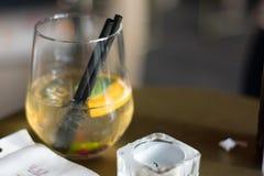 Primo piano del cocktail fresco del limone sulla tavola accanto alla piccola candela fotografie stock libere da diritti