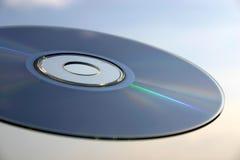 Primo piano del compact disc contro i precedenti del cielo immagini stock